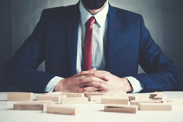 De houten kubussen van de zakenmanhand op lijst