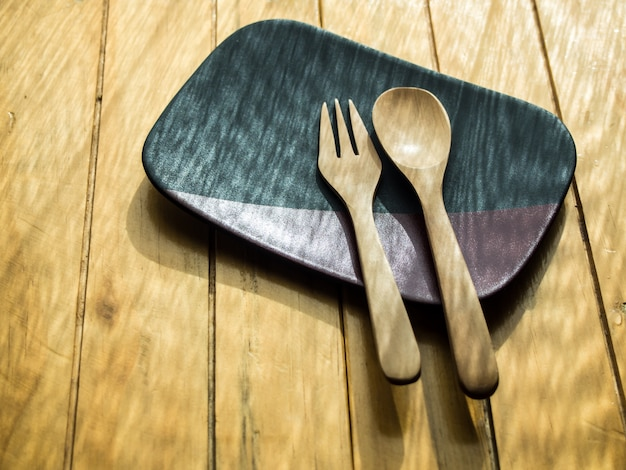 De houten lepel en folk op de zwarte en bruine plaat op de houten tafel