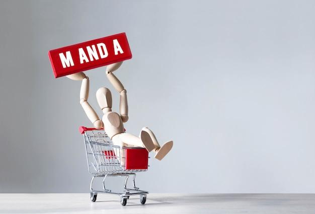 De houten man houdt een rood houten blok vast met het woord m en a, concept