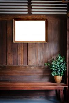 De houten omlijsting hangt op houten muurachtergrond met installatievaas op stoel.