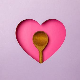 De houten oude kooklepel zit in een roze hartvormige holte. rondom is paars. ruimte kopiëren. liefde. koken. voedsel. traditie.