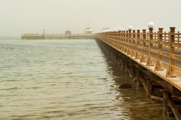 De houten pier leidt naar de schepen.