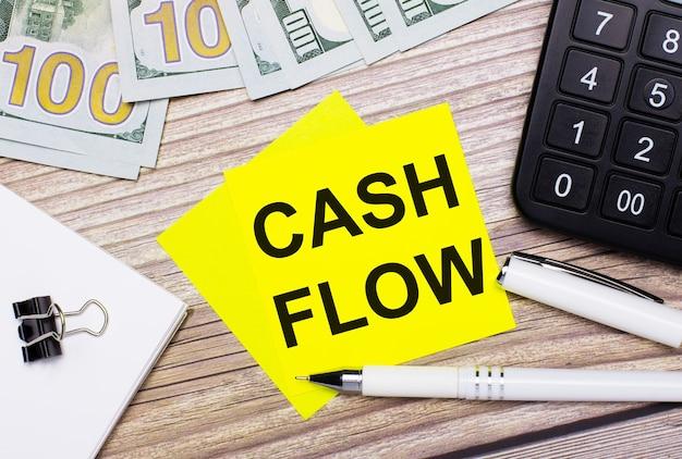 De houten tafel heeft een rekenmachine, bankbiljetten, een pen, paperclips en gele stickers met de tekst cash flow.business concept