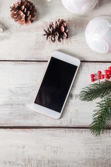 De houten tafel met een telefoon en kerstversiering.