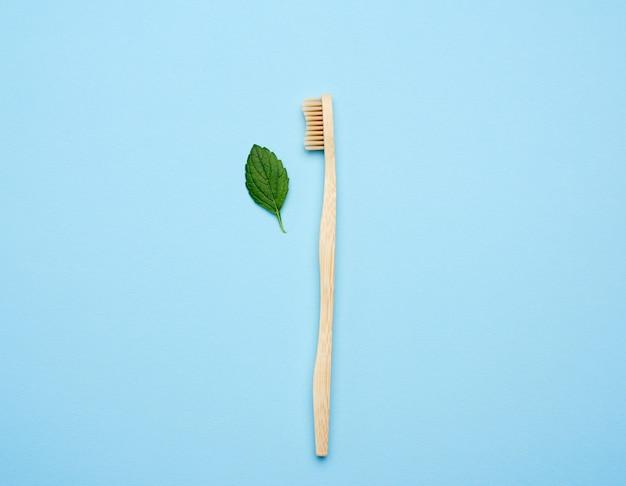 De houten tandenborstel op een blauwe achtergrond, plastic afwijzingsconcept, nul afval, legt vlak
