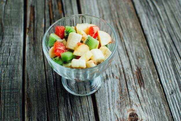 De houten textuur is een salade in een glazen container met verschillende soorten fruit