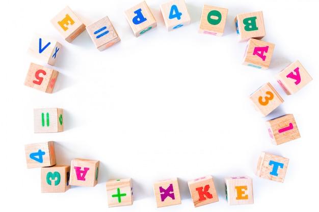 De houten welpen van het jonge geitjesspeelgoed met letters en getallen op witte achtergrond. frame van het ontwikkelen van houten blokken. natuurlijk, milieuvriendelijk speelgoed voor kinderen. bovenaanzicht plat leggen. kopieer ruimte.
