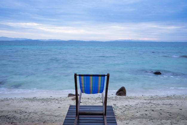 De houten wieg bevindt zich op een steigerstrand met een wit strand aan de kant van de blauwe zee