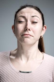 De huilende vrouw met tranen op gezicht close-up
