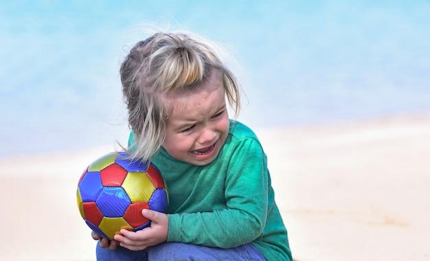 De huilende zitting van de kindbaby met kleurrijke bal op strand Premium Foto