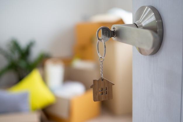De huissleutel voor het ontgrendelen van een nieuw huis is op de deur aangesloten.