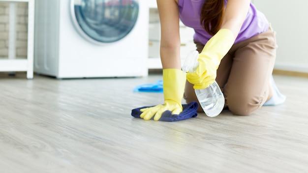 De huisvrouw spoot ontsmettingsmiddel op de vloer handhaving van concepten voor hygiëne en huiselijk leven