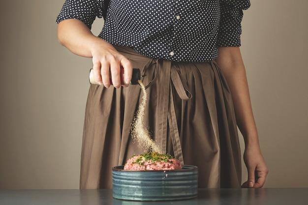 De huisvrouw van de gerichte vrouw voegt wat knoflookkruiden toe aan ongericht gehakt in blauwe ceramische kom