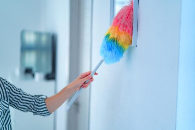 De huisvrouw veegt stof met een stofborstel tijdens de lentereiniging thuis af. huishoudelijke taken en huishouden