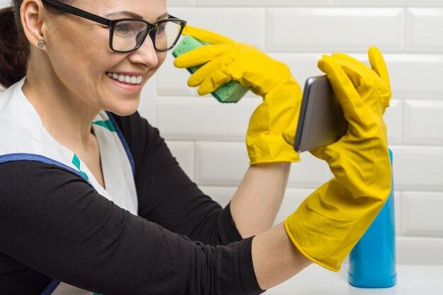 De huisvrouwenvrouw maakt in de badkamers schoon en spreekt op de telefoon.