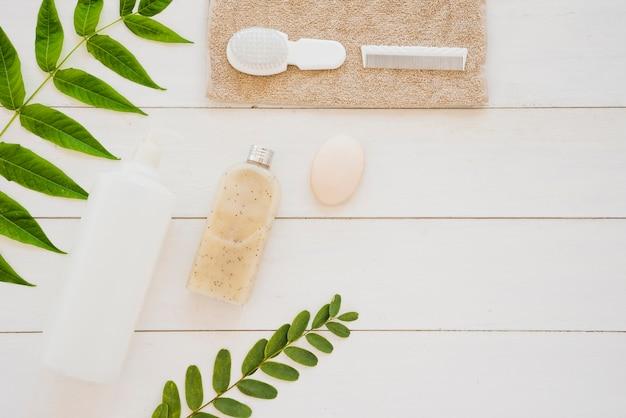De hulpmiddelen van de huidzorg op bureau met groene bladeren