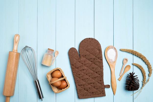 De hulpmiddelen van het bakselmateriaal op blauwe houten. ei, bloem, suiker, boter, noten over blauw. voorjaar koken thema.