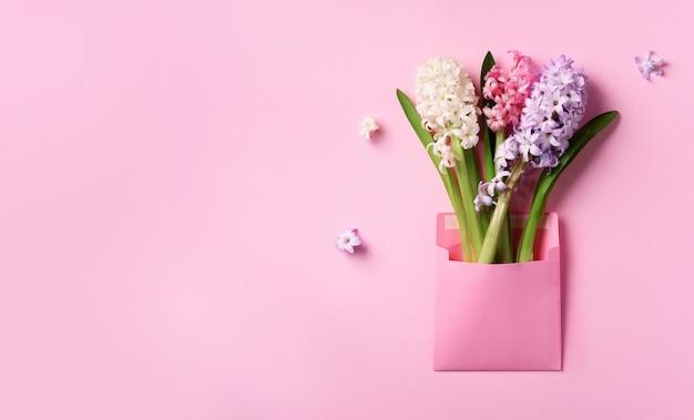 De hyacintbloemen van de lente in roze postenvelop over punchy pastelkleurachtergrond.