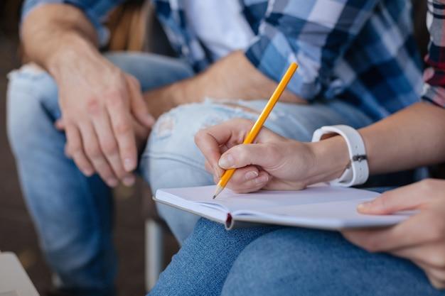 De ideeën noteren. selectieve focus van een open notebook terwijl het wordt gebruikt door een aardige aangename vrouw
