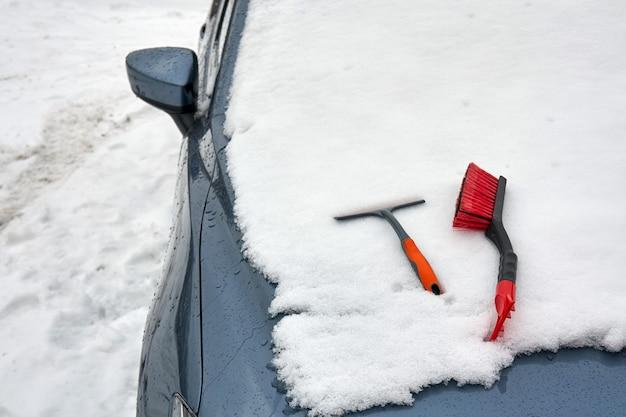 De ijskrabber en borstel voor het opruimen van de auto bevinden zich op de motorkap van de auto