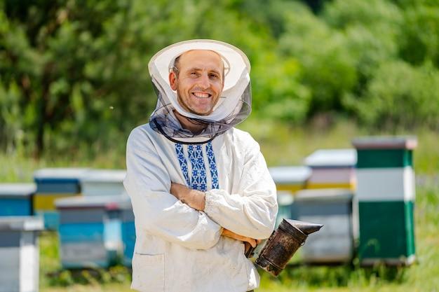 De imker staat met zijn handen in de buurt van de bijenstal. bijenteelt. bijenstal.