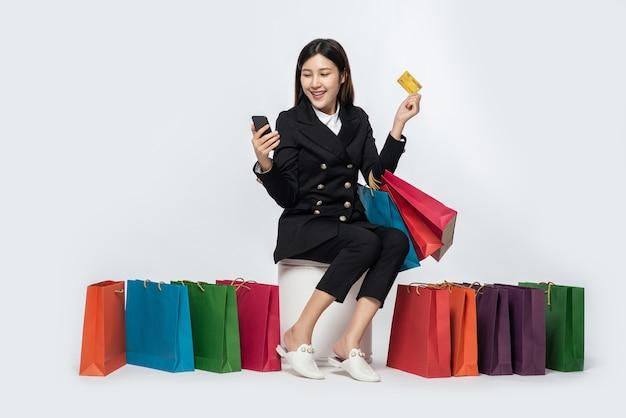 De in het donker geklede vrouw ging winkelen, met creditcards en heel veel tassen