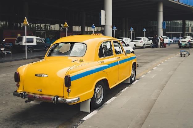 De indiase gele taxi. oude retro taxi op de parkeerplaats van de luchthaven