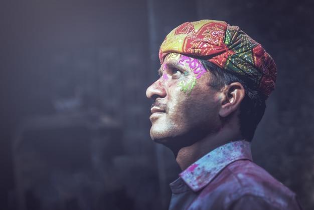 De indische mens besmeurde met kleuren op haar gezicht stelt tijdens de holi-festivalviering binnen