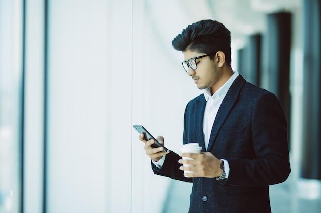 De indische zakenman gebruikt telefoon en drinkt koffie in bureau
