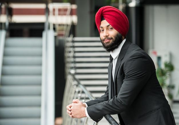 De indische zakenman in modern bureau bekijkt camera.