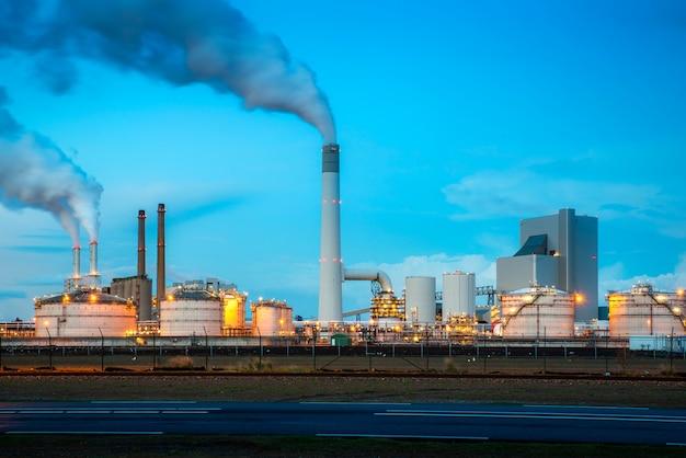 De industrie van de olieraffinaderij bij nacht in rotterdam, nederland. verontreinigingsrook van olieraffinaderijen.