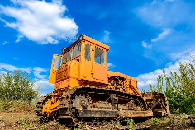 De industriële nivellerende en bewegende grond van de bouwconstructieplaatsbulldozer tijdens de wegbouw. gele bulldozer op een leemachtige bouwplaats