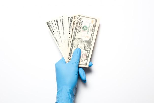 De ineenstorting van de economie als gevolg van het coronavirus. mannenhand op een witte ondergrond in medische handschoenen houdt dollars.