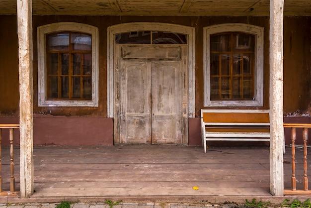De ingang van het oude houten huis, de oude bank ligt op de veranda.