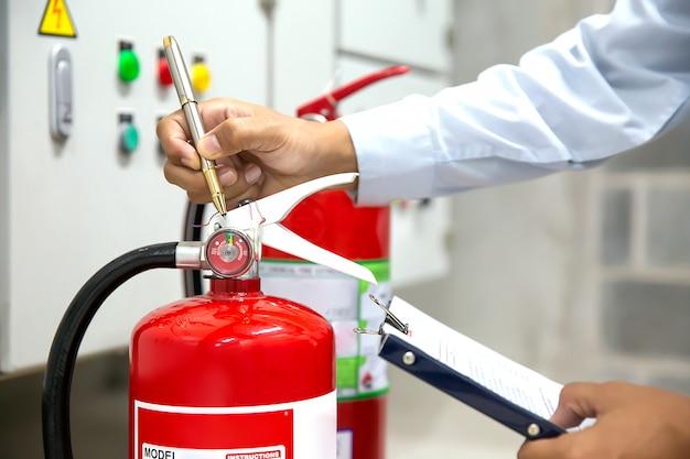 De ingenieur controleert en inspecteert rode brandblusapparaten.