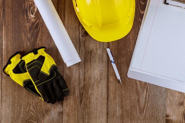 De ingenieur die van het bouwbureau aan broodjes van architectuurblauwdrukken werken huisvest plannen die de gele beschermende handschoenen van de helmveiligheid werken