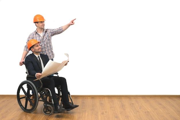 De ingenieur en het gehandicapte gebaar op de witte muurachtergrond