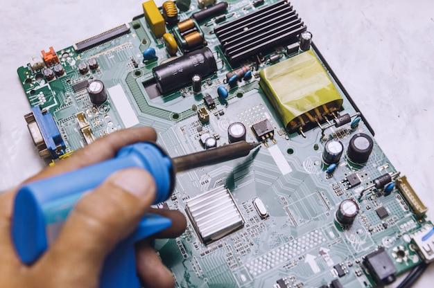 De ingenieur gebruikt soldeerbout om televisiekaart te herstellen