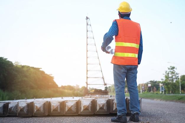 De ingenieur houdt een blauwdruk in zijn hand, kijkend naar de kraan in het bouwgebied