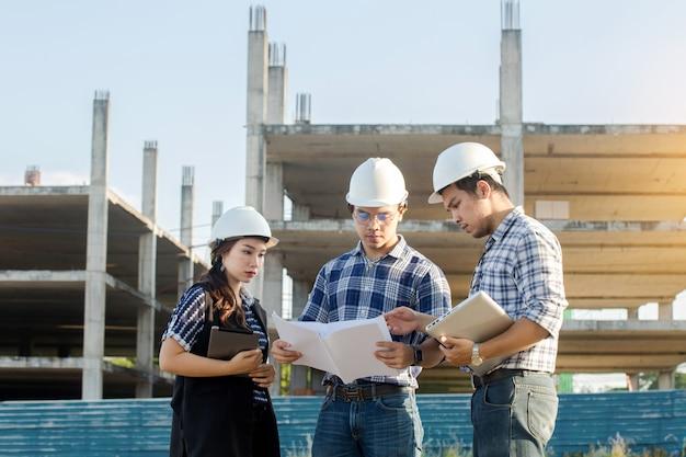 De ingenieur inspecteert bouwwerven en bespreking met bouwblauwdruk
