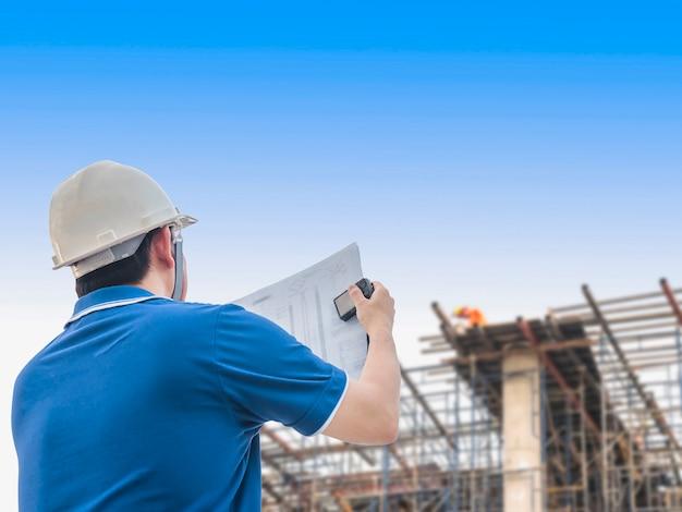 De ingenieur inspecteert zijn werk in bouwconstructieplaats