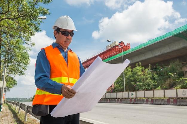 De ingenieur of de architect dragen witte helm die bouwplan werken lezen of