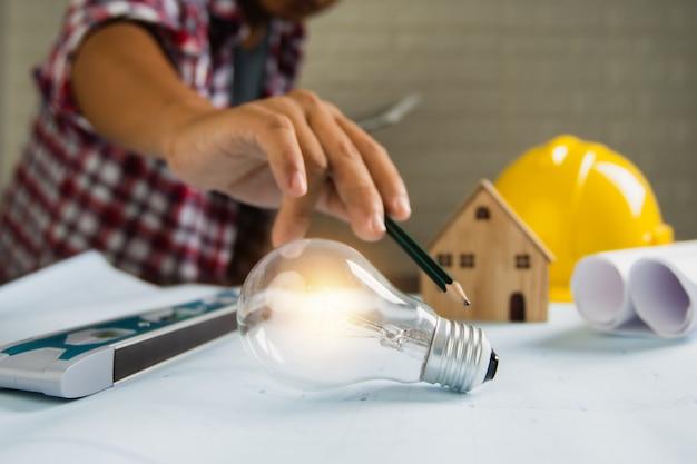 De ingenieur richt en toont gloeilamp met klein huis en bouwvoorwerpenhulpmiddelen op lijst
