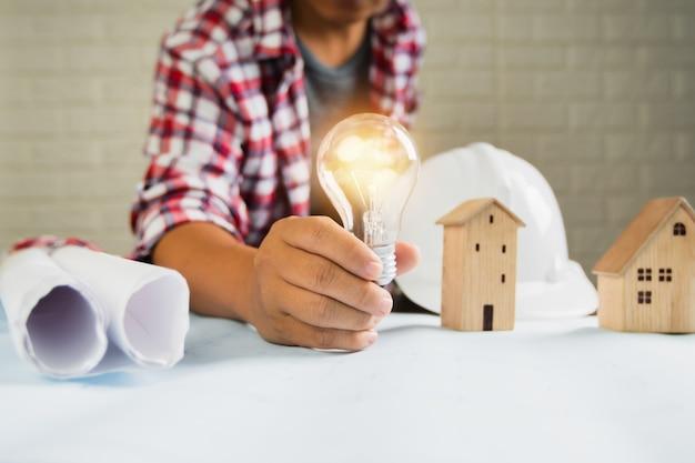 De ingenieur toont gloeilamp met klein huis en bouwvoorwerpenhulpmiddelen op lijst