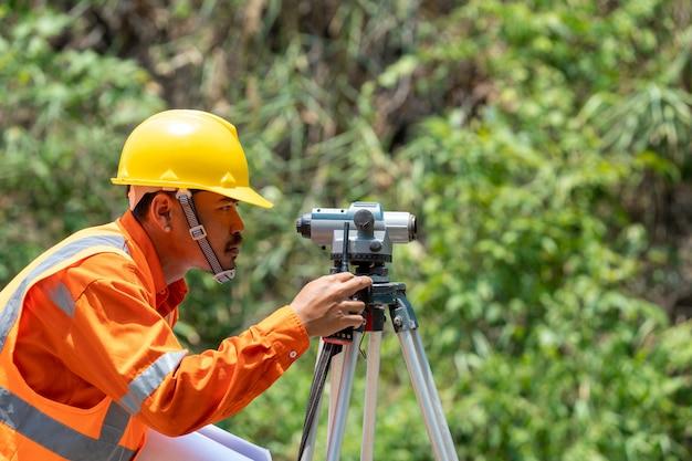 De ingenieur van de enquête in de bouwplaats gebruiken theodoliet merk op weg. ingenieurs werken op de bouwplaats.