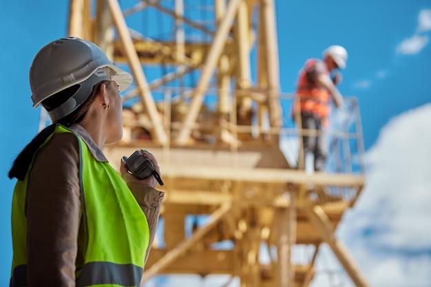 De ingenieur van meisjes met radio in hand op een bouwplaats in een beschermend vest en een harde hoed, in een arbeider op een gele kraan. selectieve aandacht
