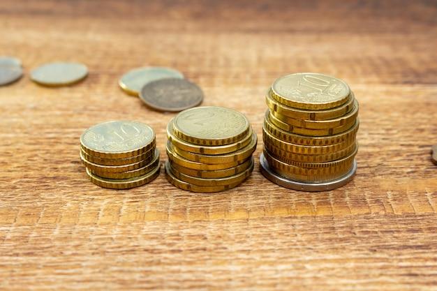De ingezette muntstukken groeien, verhogen, veranderend de euro hoop van het stapelpak op een houten achtergrond bespot omhoog selectieve nadruk dicht omhoog