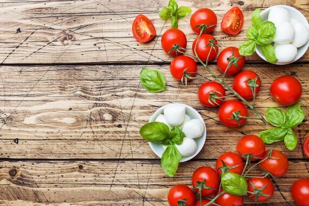 De ingrediënten voor een caprese salade. basilicum, mozzarellaballen en tomaten op houten met.
