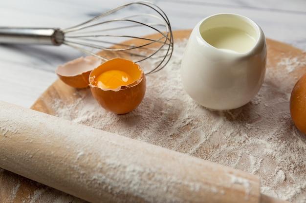 De ingrediënten voor het bakken op tafel zijn tarwebloem op een bord eieren melk en een garde