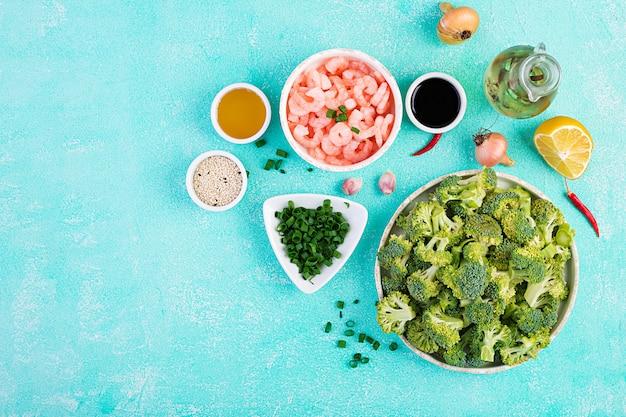 De ingrediënten voor het koken bewegen gebraden gerechtgarnalen met broccoli dicht omhoog op een lijst. garnalen en broccoli. bovenaanzicht, overhead